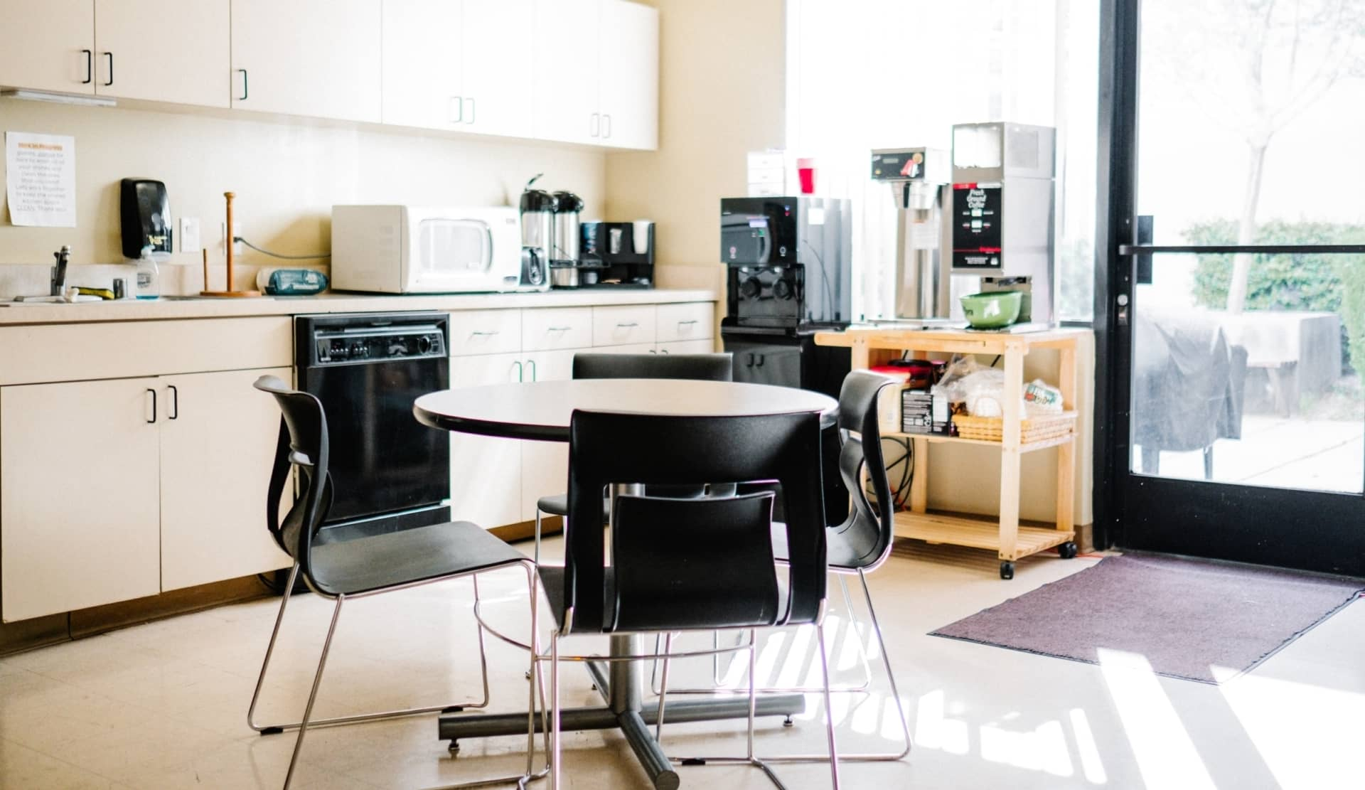 breakroom with bottleless water cooler, coffee maker and small dining table