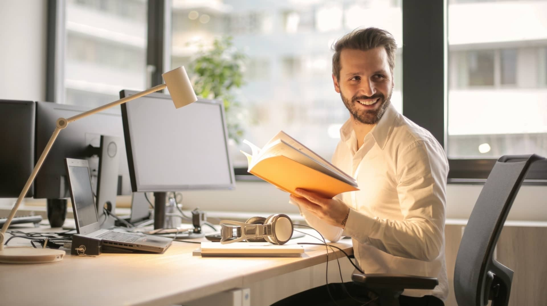 man smiling and looking back at office