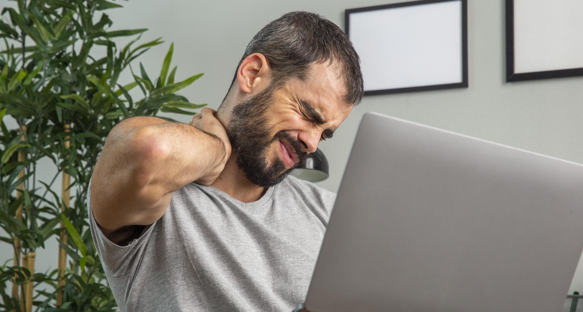 man using laptop and rubbing his neck while grimacing in pain