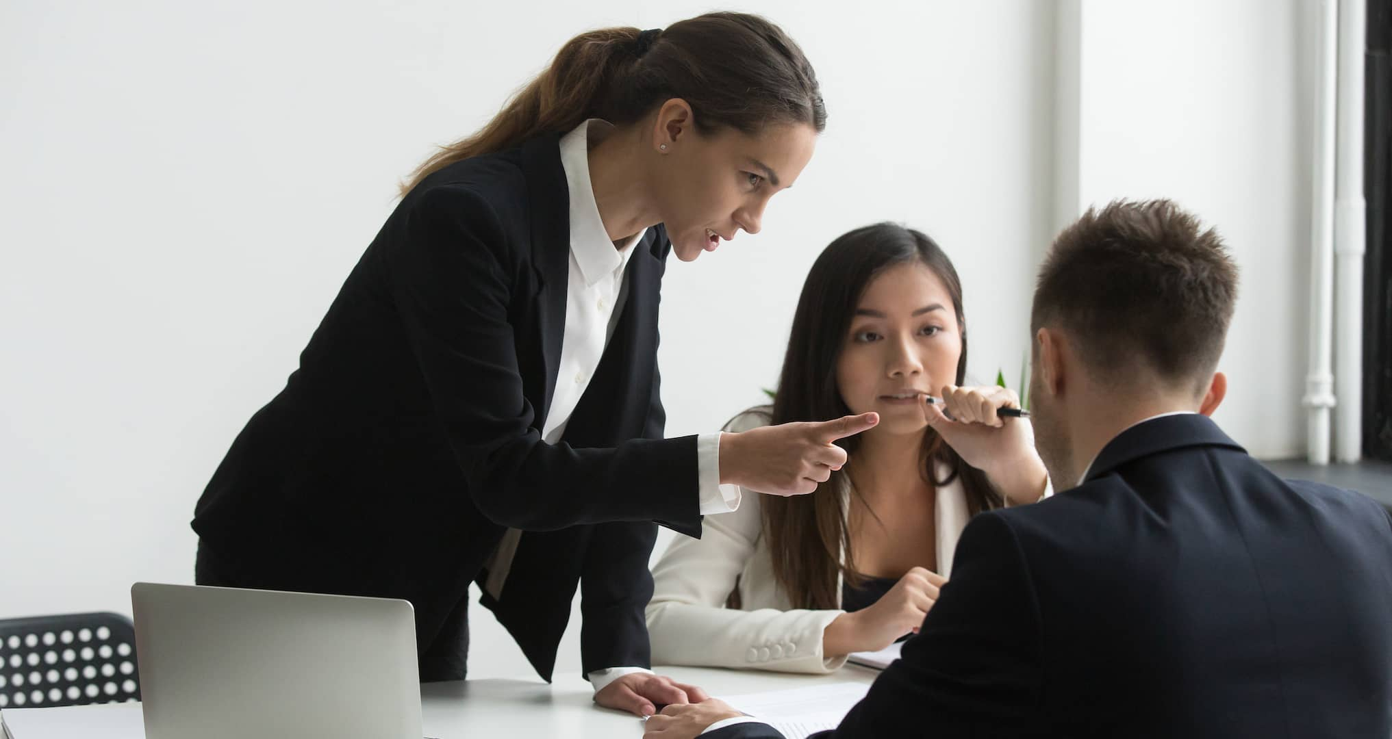 female scolding male and female employees in an office setting