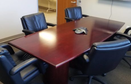 medium sized conference table and high back office chairs