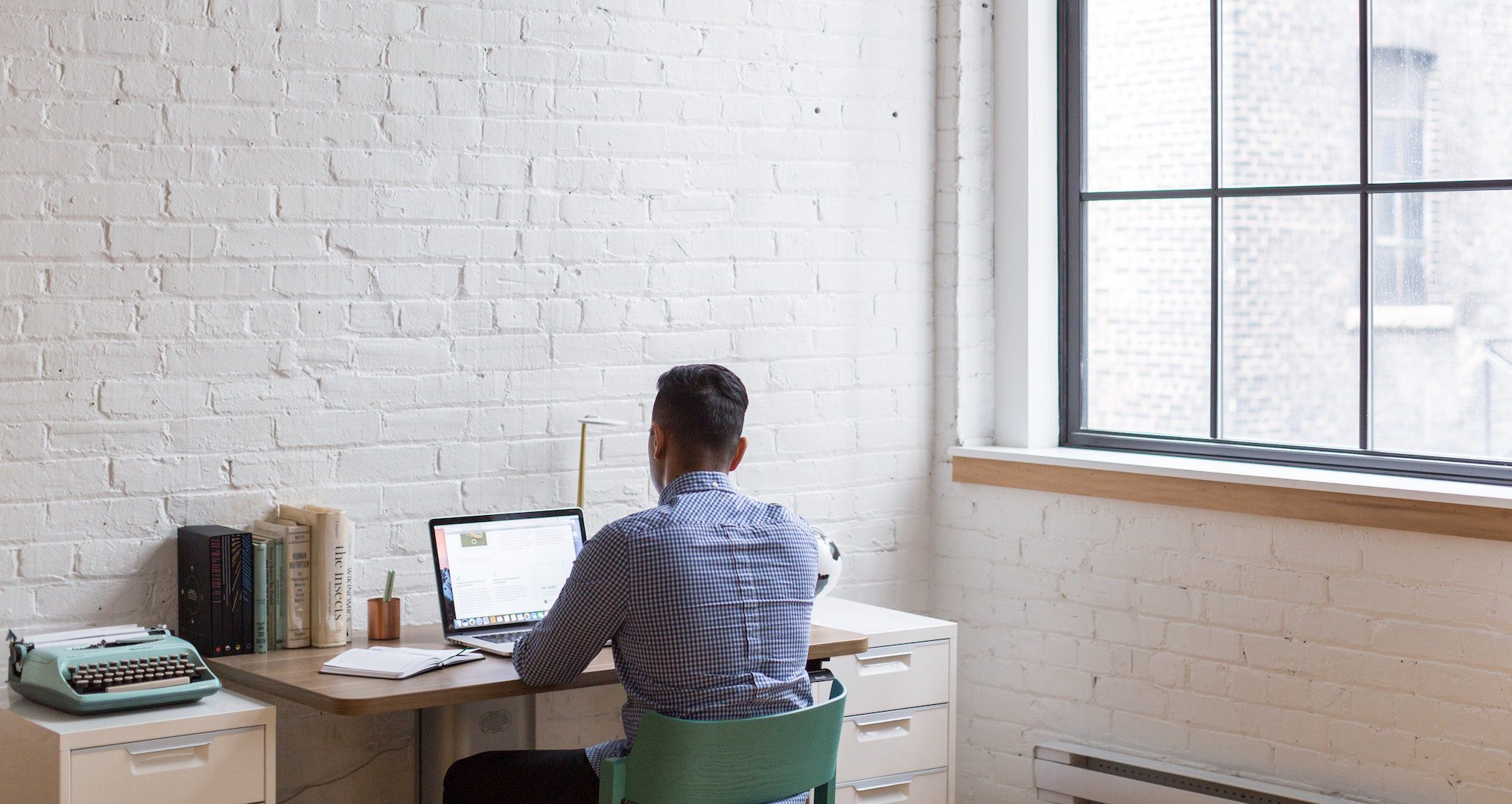 man sitting at desk working on laptop next to a large window