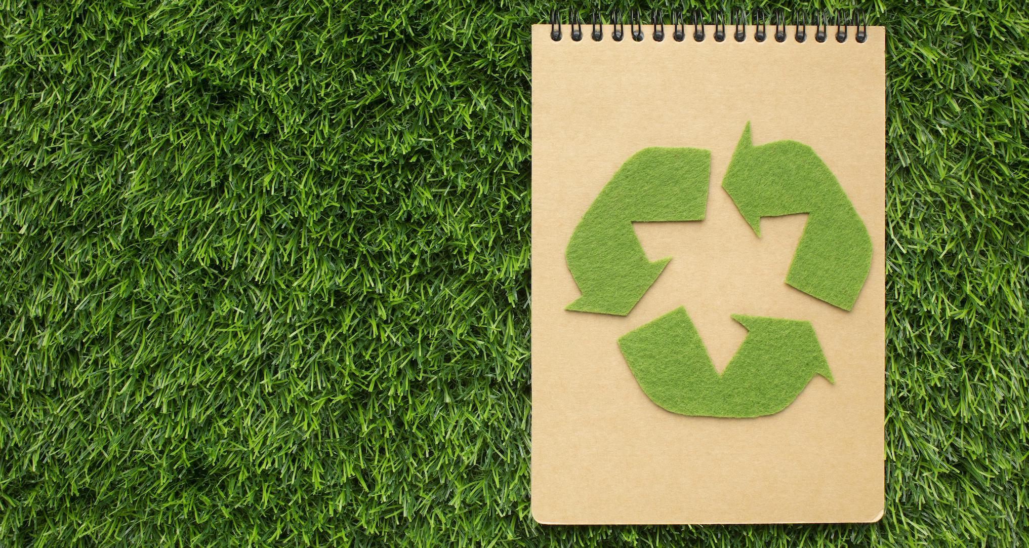 brown notebook with recycling logo on green grass background