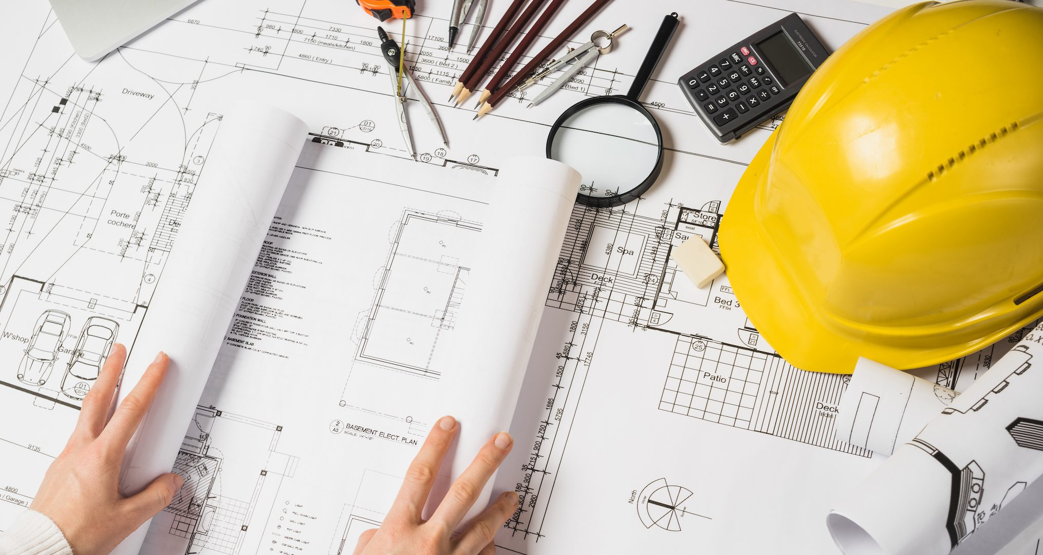 blueprints with a hard hat and drafting tools